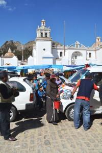 Mönch in Copacabana mit Weihwasser im Putzeimer bei der Fahrzeug-Segnung