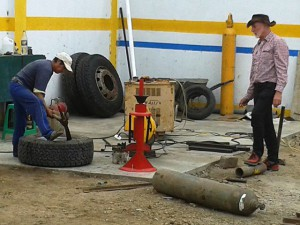 Mit der Spitzhacke wird der Reifen bei der Reparatur von der Felge gelöst.