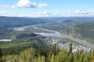 Blick über Dawson City vom Midnight Dome aus. Gut sichtbar ist das von links einströmende dunkle Wasser des Klondike, das sich zunächst nicht oder kaum mit dem viel helleren Wasser des Yukon vermischt.