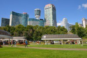Die kanadische Seite der Niagara-Fälle säumt ein großer Parkbereich. Dahinter ragen attraktiv gestaltete Hochhäuser auf.
